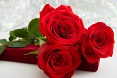 Τρία κόκκινα τριαντάφυλλα και παρόν κιβώτιο κοσμημάτων με το υπόβαθρο boke διάστημα αντιγράφων - έννοια ημέρας βαλεντίνων και των στοκ εικόνα με δικαίωμα ελεύθερης χρήσης