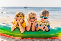 Τρία ξανθά παιδιά στα γυαλιά ηλίου βρίσκονται στην παραλία στοκ εικόνες