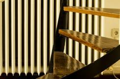 Τρία ξύλινα βήματα μιας σκάλας με την σώμα-θερμάστρα στο υπόβαθρο στοκ εικόνες