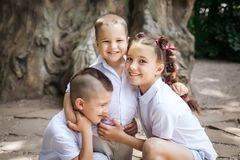 Τρία που αγκαλιάζουν τα παιδιά στοκ φωτογραφία