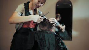 Τρίχα αγοριών περικοπών Hairstylist κατά τη διάρκεια hairdressing στο σαλόνι φιλμ μικρού μήκους