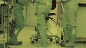 Τρεις εργαζόμενοι στο εργαστήριο Καθαρή περιοχή νανοτεχνολογία Αποστειρωμένο κοστούμι Καλυμμένος scientistе φιλμ μικρού μήκους
