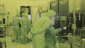 Τρεις εργαζόμενοι στο εργαστήριο Καθαρή περιοχή νανοτεχνολογία Αποστειρωμένο κοστούμι Καλυμμένος επιστήμονας φιλμ μικρού μήκους