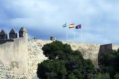 Τρεις σημαίες: Ισπανία, Andolusia και Μάλαγα στον αμυντικό τοίχο του φρουρίου Αραβικό φρούριο Gibralfaro ισπανικά Castillo de Jib στοκ φωτογραφία