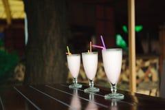 Τρεις milkshakes και καταφερτζήδες στον ξύλινο πίνακα στοκ φωτογραφίες