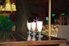 Τρεις milkshakes και καταφερτζήδες στον ξύλινο πίνακα στοκ φωτογραφία