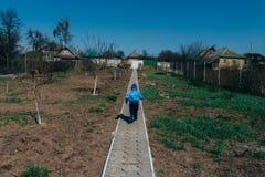 Τρεξίματα μικρά παιδιών κατά μήκος του δρόμου στο χωριό, γύρω από τα νέα δέντρα και το Η.Ε-ανασκαμμένο έδαφος, το παρθένο χώμα στοκ φωτογραφία με δικαίωμα ελεύθερης χρήσης