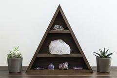 Τριγωνικό ράφι κρυστάλλου με τις Succulent εγκαταστάσεις καθεμία πλευρά σε μια ξύλινη επιφάνεια στοκ φωτογραφία με δικαίωμα ελεύθερης χρήσης