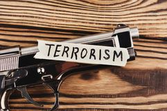 ΤΡΟΜΟΚΡΑΤΙΑ επιγραφής σε σχισμένο χαρτί και το στιλπνό πιστόλι στοκ εικόνες με δικαίωμα ελεύθερης χρήσης