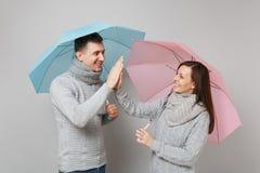 Τύπος κοριτσιών ζεύγους στα γκρίζα μαντίλι πουλόβερ μαζί κάτω από την ομπρέλα που απομονώνεται στο γκρίζο υπόβαθρο τοίχων, πορτρέ στοκ φωτογραφίες με δικαίωμα ελεύθερης χρήσης