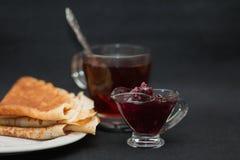 Τσάι με τη μαρμελάδα και τις τηγανίτες σμέουρων Φλυτζάνι του διαφανούς γυαλιού, της σαλτσιέρας και του άσπρου πιάτου Σκοτεινό ύφο στοκ φωτογραφίες