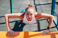Φίλαθλη νέα προκλητική γυναίκα που κάνει το ώθηση-UPS από τον πάγκο στον αθλητικό τομέα Υγιής τρόπος ζωής έννοιας στοκ εικόνα