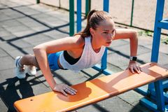 Φίλαθλη νέα προκλητική γυναίκα που κάνει το ώθηση-UPS από το χώρο αθλήσεων πάγκων Υγιής τρόπος ζωής έννοιας στοκ φωτογραφίες