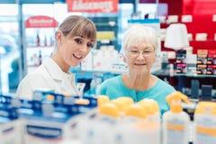 Φαρμακοποιός και πελάτης που στέκονται στο φαρμακείο μεταξύ των ραφιών στοκ φωτογραφίες με δικαίωμα ελεύθερης χρήσης