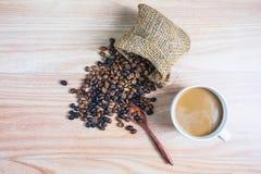 Φλυτζάνια καφέ και ψημένα φασόλια καφέ σε έναν ξύλινο πίνακα στοκ φωτογραφία με δικαίωμα ελεύθερης χρήσης