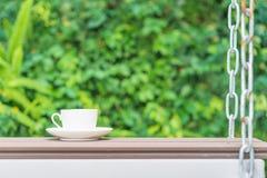 Φλυτζάνι καφέ στο κάθισμα που αναστέλλεται από τις αλυσίδες στοκ εικόνα