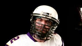 Φορέας αμερικανικού ποδοσφαίρου με το μαύρο υπόβαθρο απόθεμα βίντεο
