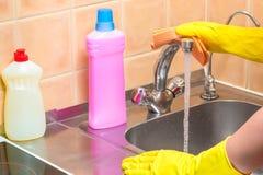 φορημένο γάντια χέρι με ένα κουρέλι και καθαρίζοντας προϊόντα στην κουζίνα κατά τη διάρκεια στοκ εικόνα με δικαίωμα ελεύθερης χρήσης