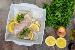 Φρέσκα ψάρια, ακατέργαστες λωρίδες βακαλάων με την προσθήκη των χορταριών και λεμόνι στοκ φωτογραφίες με δικαίωμα ελεύθερης χρήσης