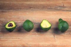 Φρέσκο τεμαχισμένο αβοκάντο Χορτοφάγος έννοια τροφίμων Ολόκληρα φρούτα αβοκάντο και δύο μισά σε μια σειρά στοκ φωτογραφίες