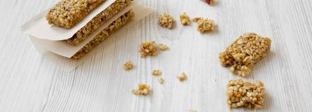 Φραγμοί Granola στο φύλλο ψησίματος σε μια άσπρη ξύλινη επιφάνεια, πλάγια όψη closeup στοκ εικόνες
