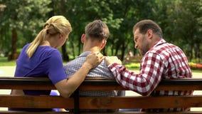 Φροντίζοντας μητέρα και μπαμπάς που υποστηρίζουν τη λυπημένη συνεδρίαση γιων εφήβων στον πάγκο στο πάρκο, κρίση στοκ εικόνες με δικαίωμα ελεύθερης χρήσης