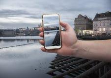 Φυσική άποψη του ιστορικού κέντρου Πράγα, γέφυρα του Charles και κτήρια του παλαιού πόλης χεριού με ένα smartphone, στην οθόνη το στοκ εικόνα