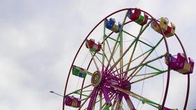 Φωτισμένη ρόδα Ferris με τις πολύχρωμες καμπίνες που γυρίζουν στο λούνα παρκ απόθεμα βίντεο