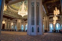 Φωτισμένος πολυέλαιος στο μεγάλο μουσουλμανικό τέμενος Muscat με πιστό και το turiusti Ομάν στοκ φωτογραφία