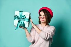 Φωτογραφία της όμορφης γυναίκας στο καπέλο πιλήματος που κρατά το παρόν κιβώτιο δώρων στοκ φωτογραφία με δικαίωμα ελεύθερης χρήσης
