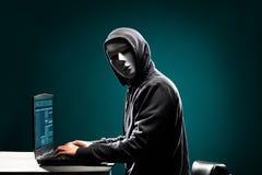 Χάκερ υπολογιστών στην άσπρη μάσκα και hoodie Κρυμμένο σκοτεινό πρόσωπο Κλέφτης στοιχείων, απάτη Διαδικτύου, darknet και cyber ασ στοκ φωτογραφίες
