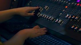 Χέρια γυναίκας στην κονσόλα μίξης που αναμιγνύει τις διαδρομές στο disco απόθεμα βίντεο