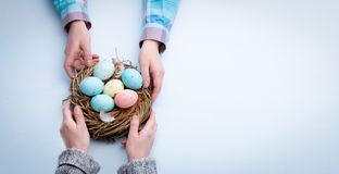 Χέρια γυναικών που παίρνουν τα χρωματισμένα αυγά Πάσχας στοκ φωτογραφία με δικαίωμα ελεύθερης χρήσης