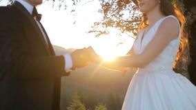 Χέρια εκμετάλλευσης γαμήλιων ζευγών στο υπόβαθρο ηλιοβασιλέματος που πυροβολείται σε σε αργή κίνηση όμορφα βουνά απόθεμα βίντεο