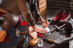 Χέρια της Cobber με ένα μολύβι σε ένα γραφείο στοκ εικόνα