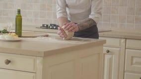 Χέρια του νέου κατασκευαστή πιτσών στο μάγειρα ομοιόμορφο skillfully και γρήγορα kneeding ζύμη για την πίτσα στη σύγχρονη κουζίνα απόθεμα βίντεο