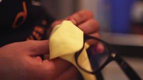 Χέρι κινηματογραφήσεων σε πρώτο πλάνο μιας μαλακός-εστίασης φακών γυαλιών καθαρισμού ατόμων στο υπόβαθρο απόθεμα βίντεο