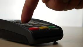 Χέρι με το ισχυρό κτύπημα πιστωτικών καρτών μέσω του τερματικού για την πώληση και της πληρωμής για τη διαταγή απόθεμα βίντεο
