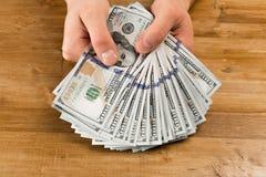 Χέρι, δολάρια ΗΠΑ χρημάτων - εικόνα στο ξύλινο υπόβαθρο στοκ εικόνα