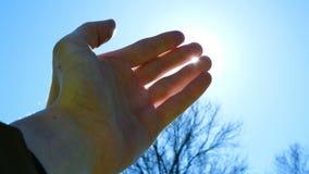 Χέρι των παιχνιδιών δάχτυλων ατόμων με τις ακτίνες του ήλιου ενάντια στο μπλε ουρανό απόθεμα βίντεο