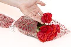 Χέρι που κρατά μια ανθοδέσμη των τριαντάφυλλων σε ένα άσπρο υπόβαθρο στοκ εικόνες με δικαίωμα ελεύθερης χρήσης