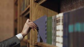 Χέρι που παίρνει το βιβλίο από το ράφι Εικόνα ενός χεριού που επιλέγει το βιβλίο από ένα ράφι Μαζεμμένα με το χέρι βιβλία στα ράφ απόθεμα βίντεο