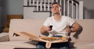 Χαλαρώνοντας άτομο που τρώει την πίτσα και που προσέχει τη TV απόθεμα βίντεο