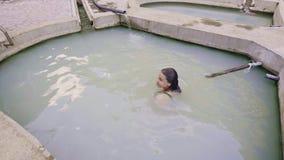 Χαλαρώνοντας γυναίκα που κολυμπά στη λίμνη μεταλλικού νερού στο υπαίθριο θέρετρο SPA Ευτυχής γυναίκα που απολαμβάνει το θερμικό λ φιλμ μικρού μήκους