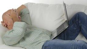 Χαλαρωμένος επιχειρηματίας που μένουν στον καναπέ στη διαβίωση και εργασία που χρησιμοποιούν το lap-top στοκ φωτογραφία με δικαίωμα ελεύθερης χρήσης