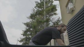 Χαλαρωμένο ευτυχές άτομο εφήβων στις αποσκευές εκφόρτωσης διακοπών από το αυτοκίνητο hatchback που φθάνει στον προορισμό - φιλμ μικρού μήκους