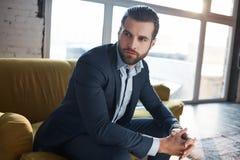 Χαμένος στις επιχειρησιακές σκέψεις Ο στοχαστικός όμορφος νέος επιχειρηματίας σκέφτεται για την επιχείρηση καθμένος στον καναπέ στοκ εικόνες με δικαίωμα ελεύθερης χρήσης