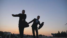 Χαμηλή άποψη γωνίας δύο ευτυχών νέων συναδέλφων με τον αστείο χορό χαρτοφυλάκων περπατώντας μετά από την επιτυχή επιχειρησιακή δι φιλμ μικρού μήκους