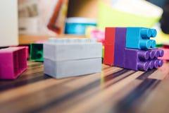 Χαμηλή άποψη γωνίας σχετικά με το παιχνίδι κατασκευής τούβλου κύβων στο πάτωμα στοκ φωτογραφία