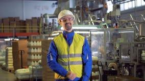 Χαμογελώντας άνδρας εργαζόμενος στη λειτουργούσα δυνατότητα εργοστασίων απόθεμα βίντεο